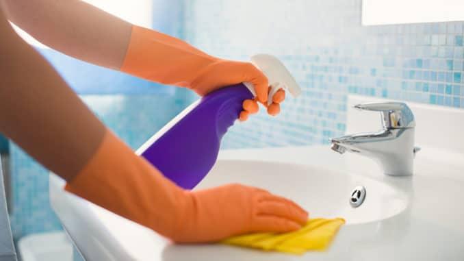 Eine Frau putzt das Waschbecken