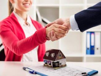 Immobilienmaklerin und Käufer schütteln Hände