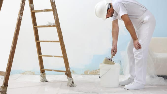 Der Maler streicht eine Wand
