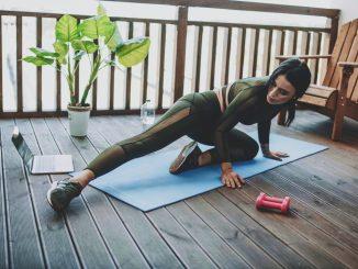 Frau macht Gymnastik auf einer Holzterrasse